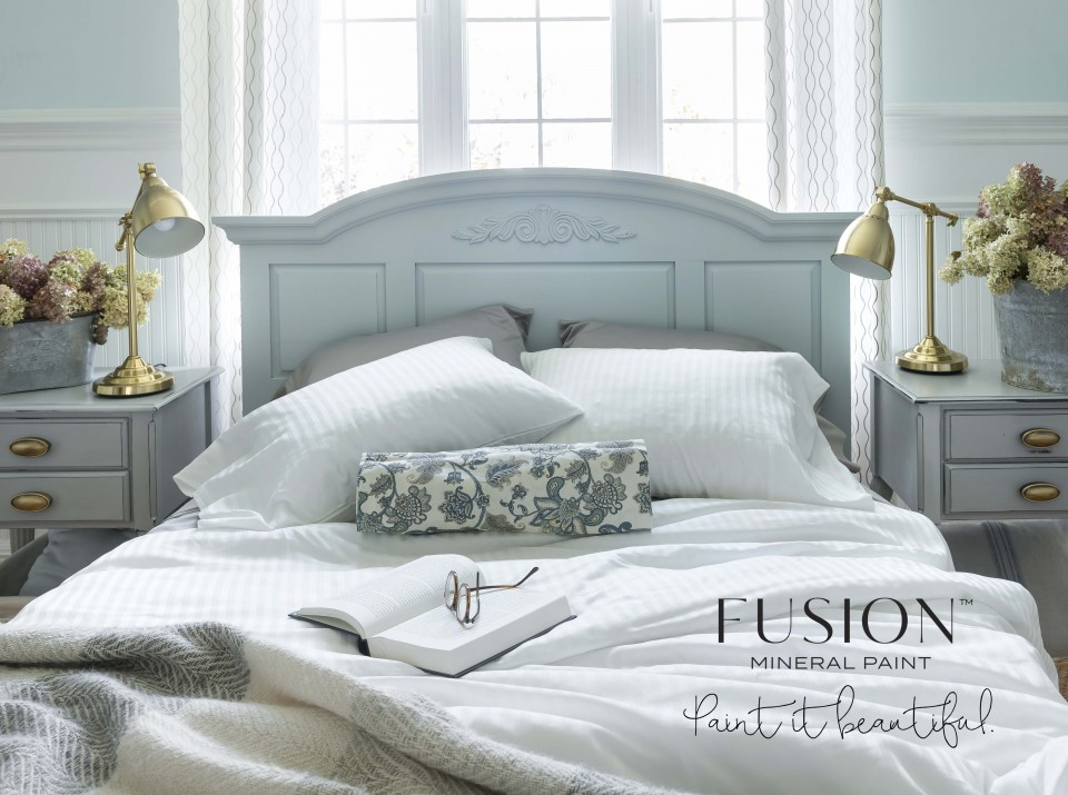 The fully painted headboard is the focus of the image, now attached to a bed with fluffy pillows and ruffled covers. The scene is very serene and cozy-looking.
