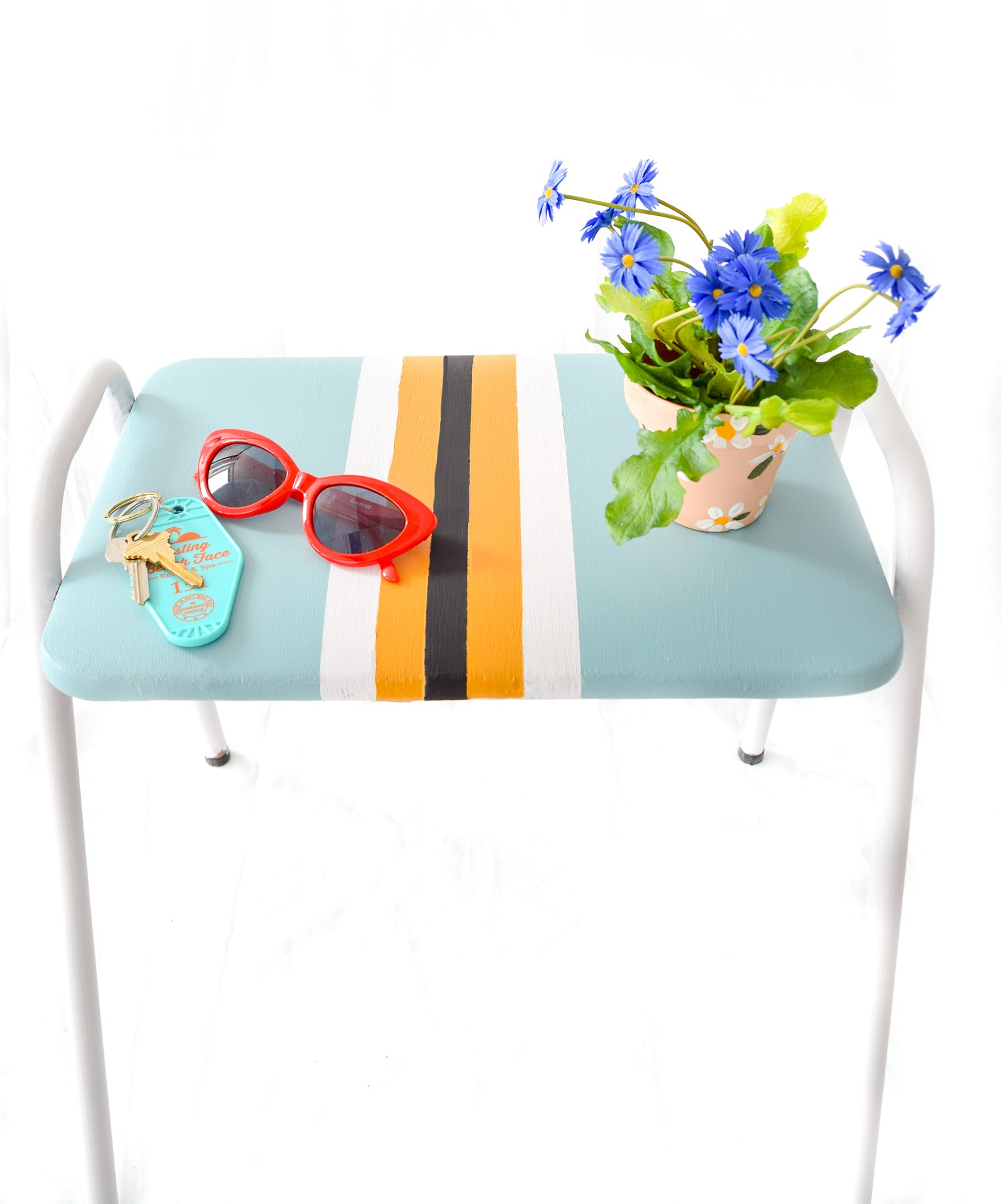 Blue and yellow stool with red glasses and plant on it