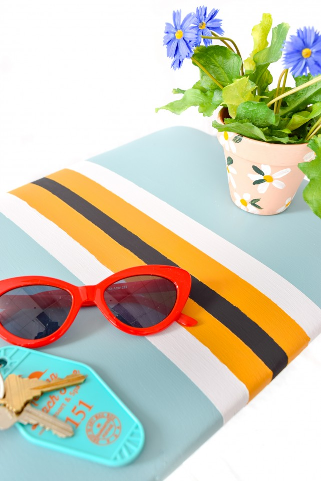 red sunglasses on a vintage striped stool