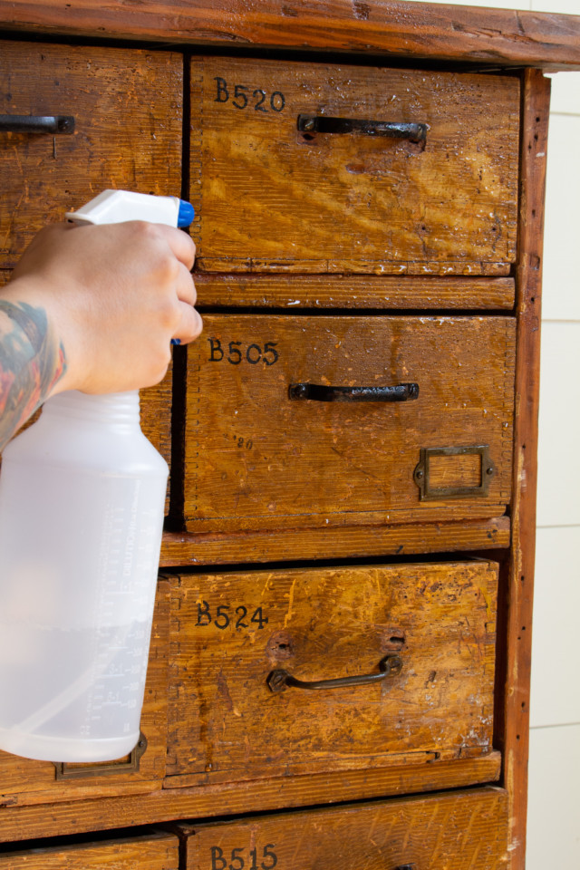 Spraying with TSP to clean the wooden piece of furniture