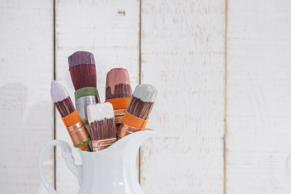 Jug of brushes with paint dripping on them
