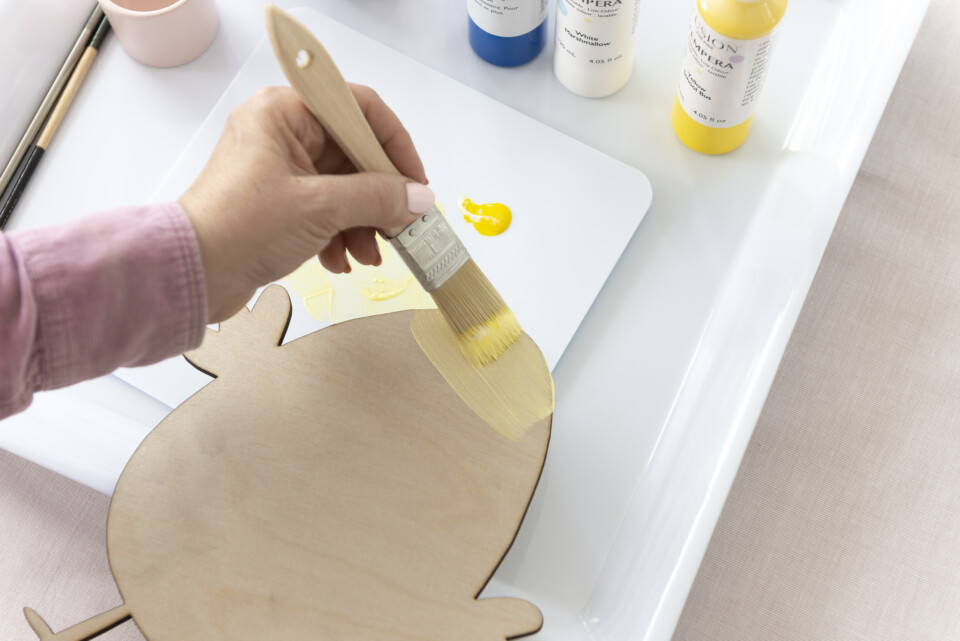 painting wood cut out of chicken with yellow paint