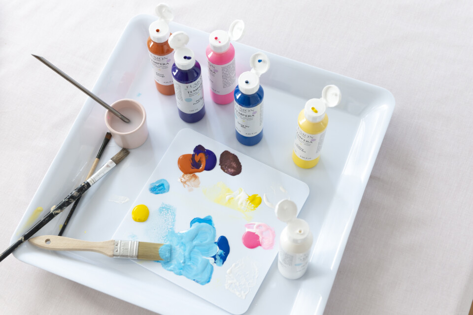 open pots of paint on a tray, brushes and brushstrokes of colour