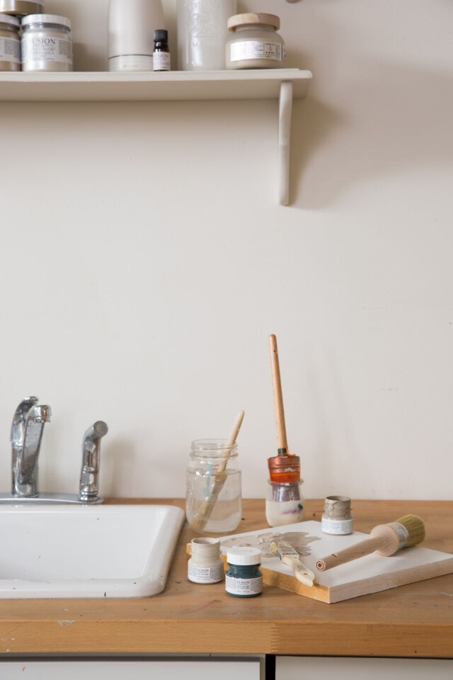 Paint and brushes beside a sink